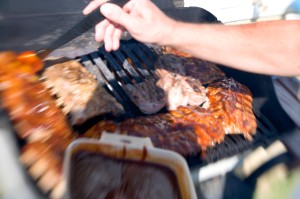 A man bastes meat on a barbecue grill