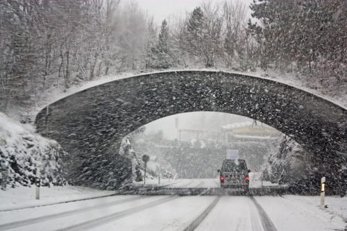 Photo of car on snowy road.