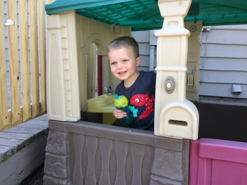 A young boy playing outside in a play house