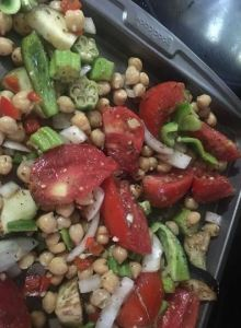 Skillet of roasted vegetables with okra, tomatoes, onions, and beans