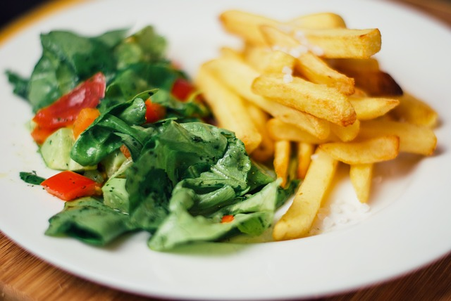 a plate with salad on one half and French fries on the other