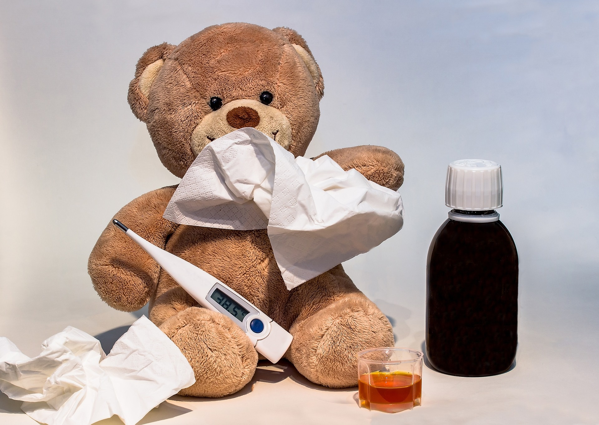Teddy bear with tissues, thermometer, and cough medicine