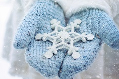 Hands with blue mittens on holding a snow flake