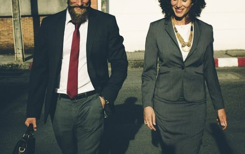 man and woman in business attire out for a walk