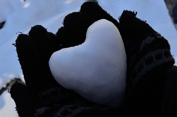 two hands with mittens holding a heart-shaped snowball