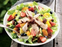 Salad with chicken, strawberries, nuts, oranges. Seasonal foods.