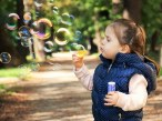 Picture of little girl blowing bubbles outside