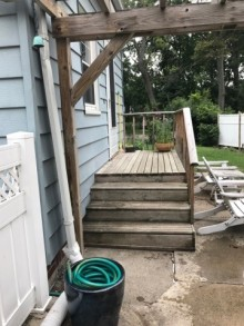 photo of porch and sidewalk and hose contained in a large blue planter
