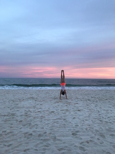 girl doing handstand on beach with sunset/ocean in background