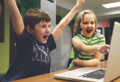 excited kids looking at a computer