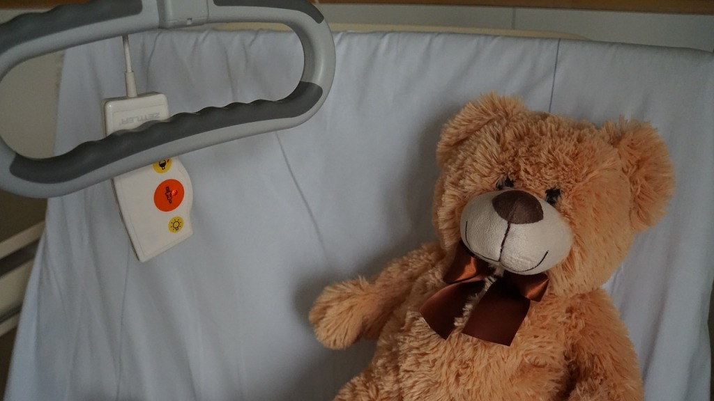 picture of teddy bear in hospital bed