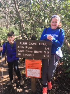 Two children in hiking clothes next to a sign that says Alum Cave Trail. Trees are in the background.