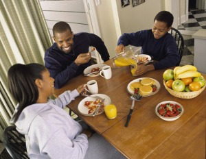 Family eating pancakes and fruit