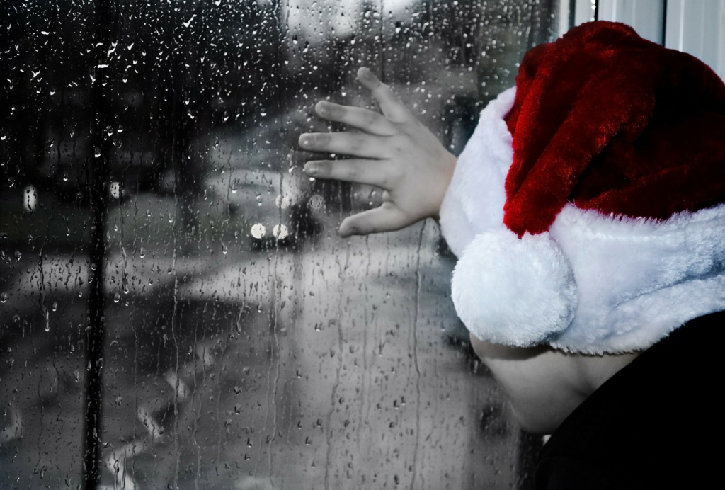Child in Santa hat looking out the window on a rainy day