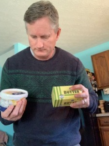 Man looking at butter and margarine