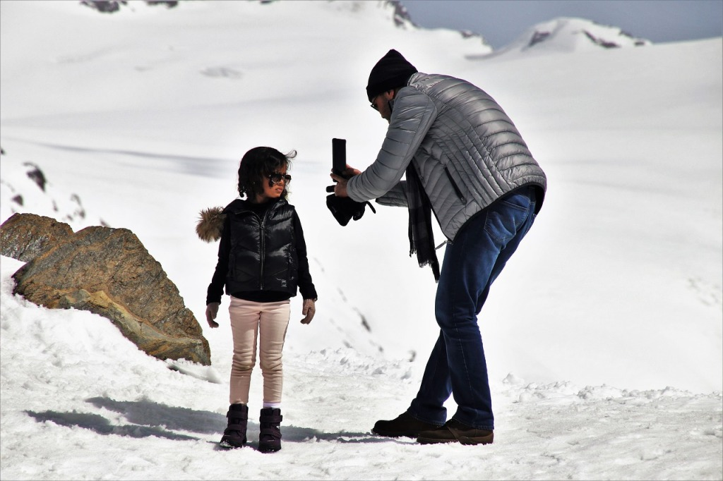 Father taking photo of daughter playing in snow.