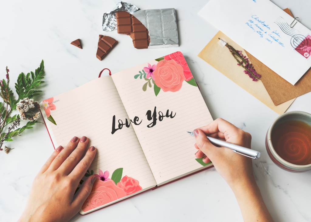 "Woman writing ""Love You"" in a journal. Letters and chocolate bar."
