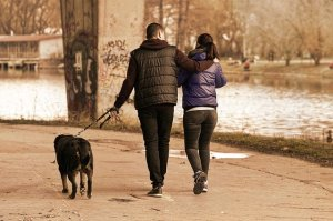 a couple walking outdoors, dressed in winter coats