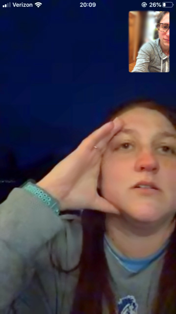 Girl with hand on forehead - a screen shot from a facetime phone call