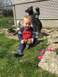 A toddler sitting in the grass with plastic Easter eggs
