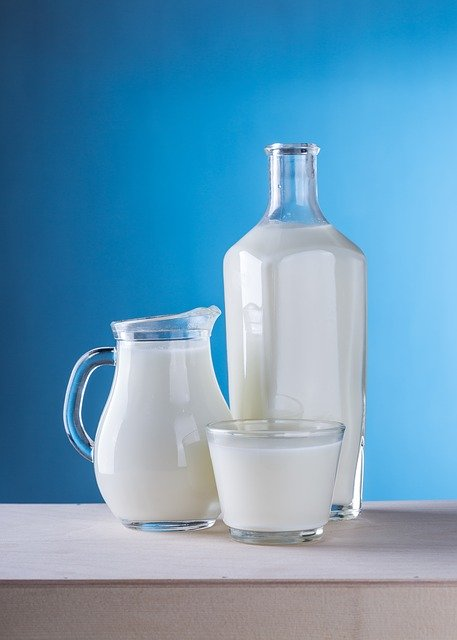 3 milk in glass containers with a blue background
