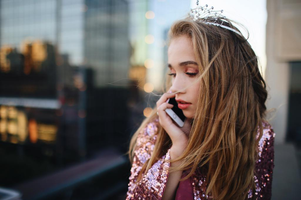 Teenage girl wearing sparkly pink clothing and a tiara, talking on a cell phone.