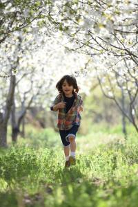 Child running outside under flowering trees