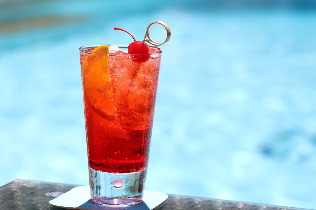 clear glass with a red colored beverage sitting on a pool ledge