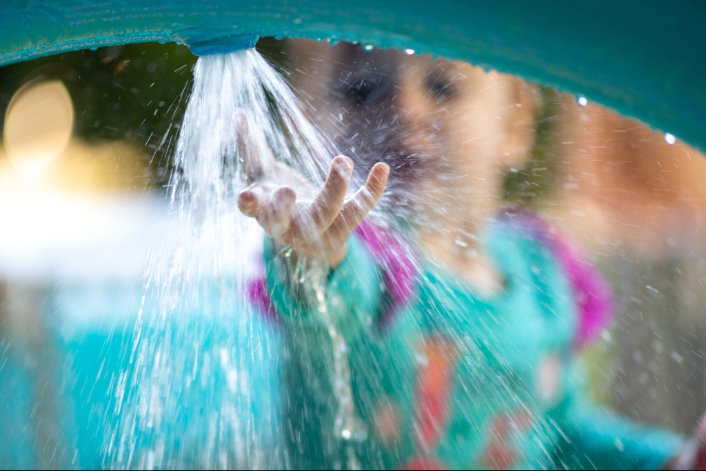 Child playing in spraying water