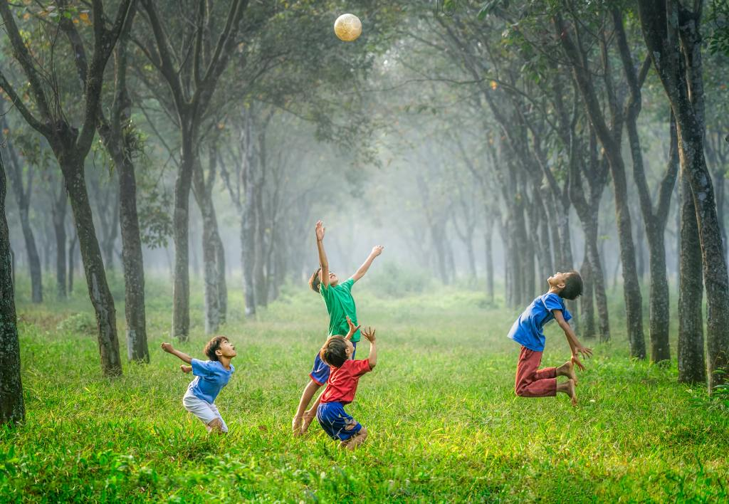 Children paying ball outside in a grove of trees