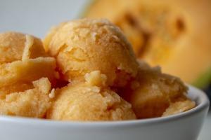 Scoops of orange colored sorbet or sherbet in a bowl