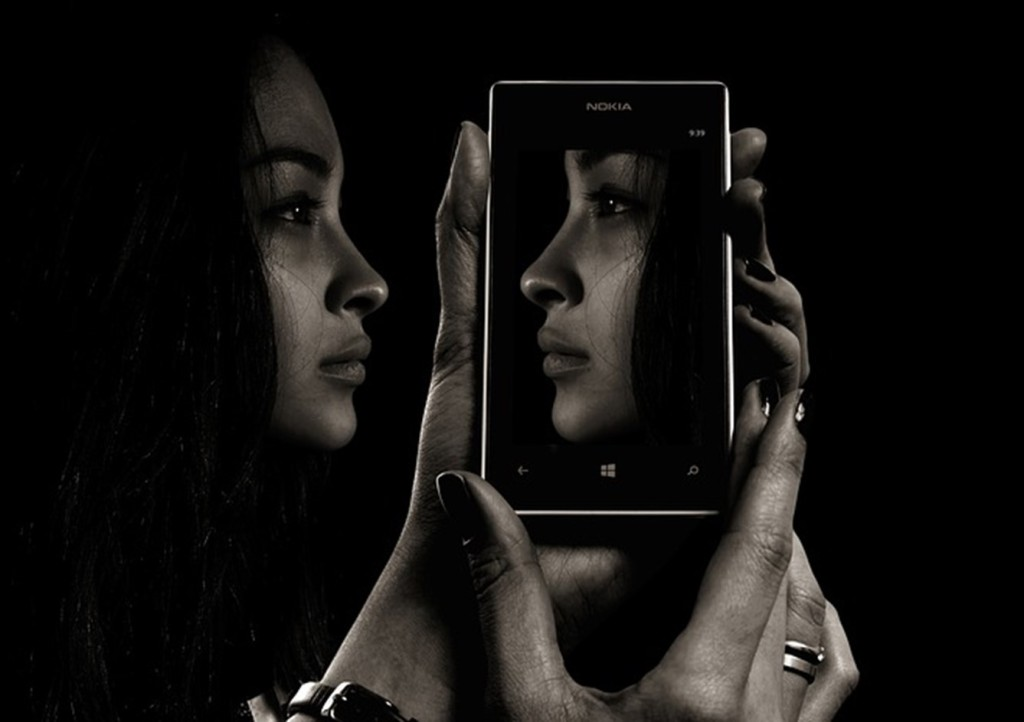 Person holding cell phone with reflection of own face
